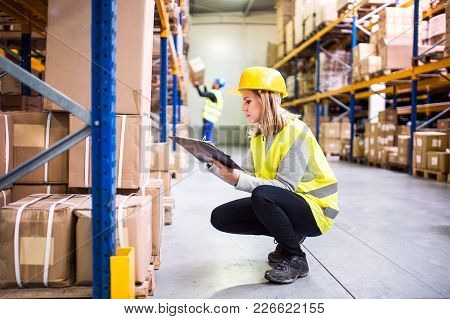 Young Woman Worker Or Supervisor With Clipboard. Warehouse Workers Controlling Stock.