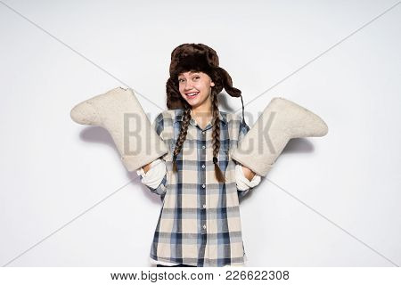 Smiling Russian Girl In A Plaid Shirt And A Hat With Ear-flaps Holds Gray Warm Felt Boots