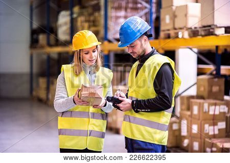 Young Warehouse Workers With Barcode Scanner Working Together. Man And Woman Discussing Something.