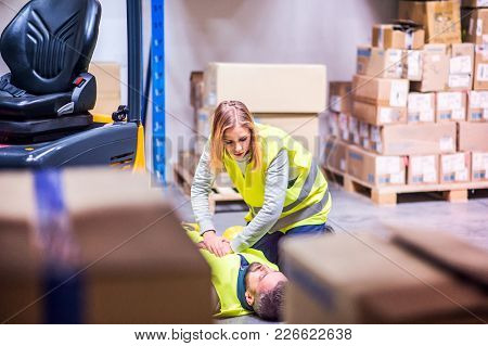 An accident in a warehouse. Woman performing cardiopulmonary resuscitation. Man lying on the floor. poster