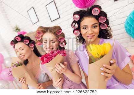 Three Girls With Curlers In Their Hair And Flowers In Hands. They Are Celebrating Women's Day March