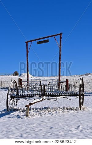 An Old Steel Rake Left In The Snow On A Ranch Pasture