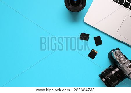 Top View Of A Desktop Of A Photographer Consisting On A Camera, A Laptop, A Notebook And A Memory Ca