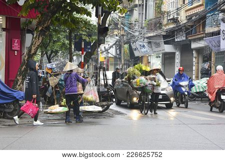 Hanoi, Vietnam - December 13th 2017. Street Vendors Selling From Bikes And Carrying Poles/shoulder P
