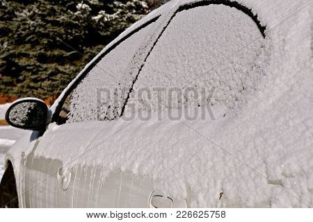 A White Car Is Covered With A Layer Of White Snow