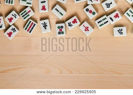 White-green Tiles For Mahjong On A Brown Wooden Background. Empty Space From Below