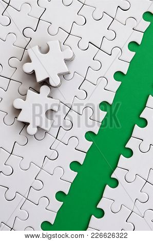 The Green Path Is Laid On The Platform Of A White Folded Jigsaw Puzzle. The Missing Elements Of The