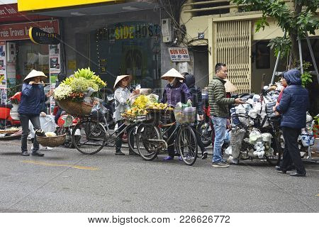 Hanoi, Vietnam - December 13th 2017. Street Sellers Sell Fruit And Flowers From Their Bikes In The H