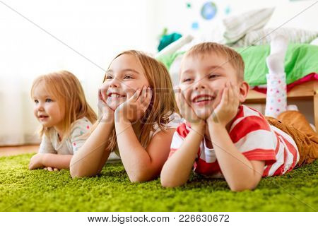 childhood, leisure and family concept - happy little kids lying on floor or carpet