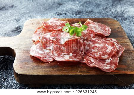 Thinly Sliced Salami On A Wooden Texture On The Background.