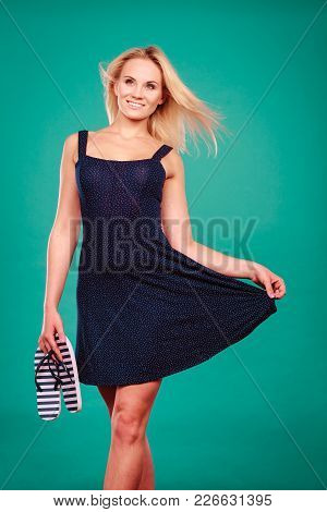 Summer Trendy Fashionable Outfit Ideas Concept. Woman Wearing Short Navy Dress Holding Flip Flops