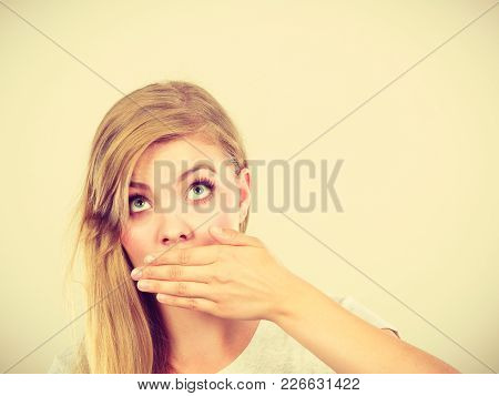 Saying Bad Things, Shocking News Concept. Ashamed Young Blonde Woman Having Hand On Her Mouth