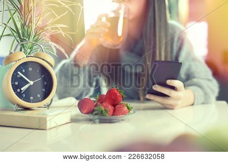 Healthy Breakfast Of Strawberries At Home Kitchen, Defocused Woman Drinking Tea And Surfing On Her M