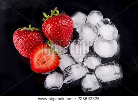 Ice Cubes With Strawberries On Black Background