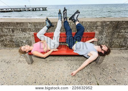 Young Tired People Friends In Training Suit With Roller Skates. Woman And Man Relaxing Lying On Benc