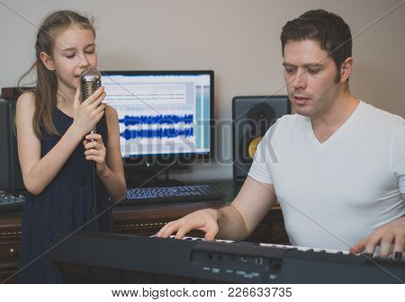 Man With Little Girl Rehearsing Song In Music Studio.