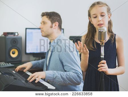 Man With Little Girl Rehearsing Song In Music Studio. Focused On Girl.