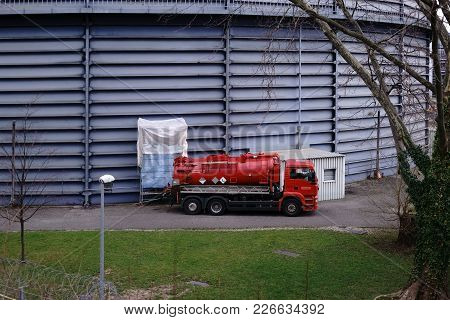A Red Truck Is Parked At A Water Storage Tank Of A Power Station.