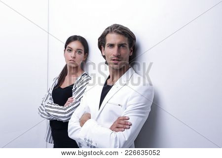 upset couple leaning on a white wall
