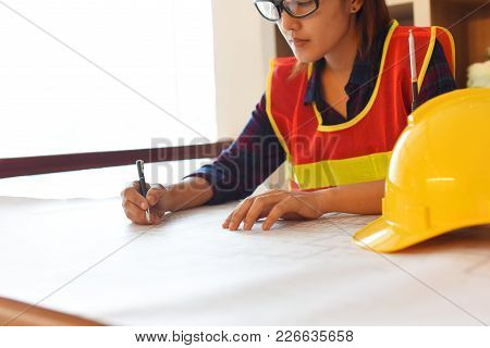 Professional Safety Engineer , Young Asian Female  Working At Her Office  Wears Safety Equipment And