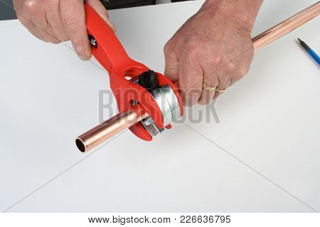 Plumber Cutting Copper Pipe With A Special Cutting Tool.