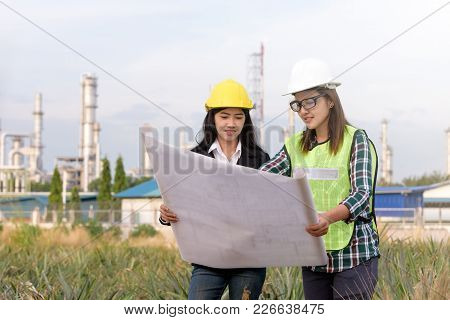 Asian Architects Team With Hardhat And Safety Jacket On Construction Site Check Documents Plan On Co
