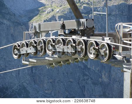 Cable Car Gear Wheels With Mountains Background . Rollers And Pulleys Of The Ski Lift