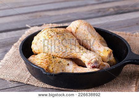Raw Chicken Legs In A Frying Pan On A Table. Meat Ingredients For Cooking.