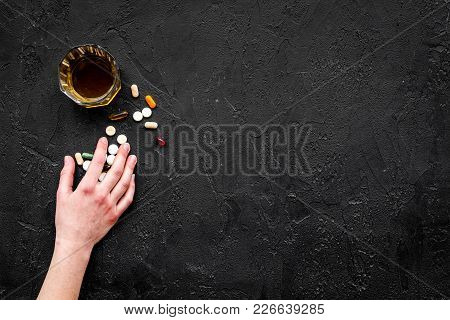 Hungover Syndrome. Alcoholism. Glass And Pills On Black Background Top View.