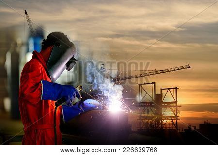 Double Exposure Of Industrial Worker At The Factory And And Silhouette Tower Cranes Build Large Resi