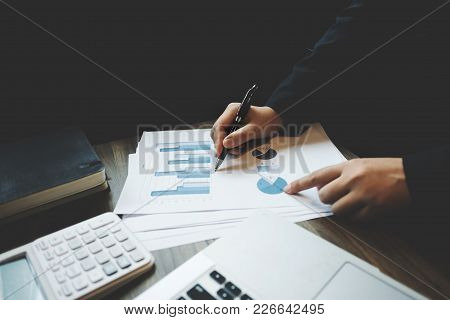 Image Of Bookkeeper /  Financial Inspector Calculating On Investment Data With Documents And Laptop