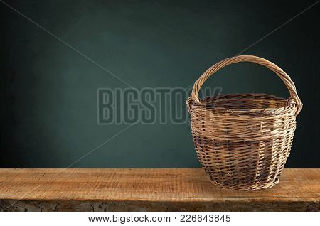 Isolated Basket. One Vintage Wicker Basket On A Shelf  Isolated On Black Background