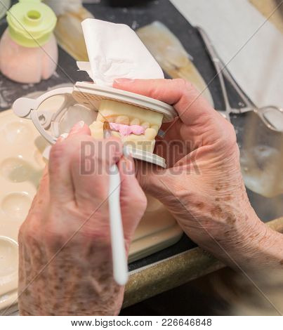 Female Dental Technician Applying Porcelain To A 3D Printed Implant Mold In The Lab.