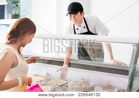 Young deli assistant serving a customer pointing to a selection of food in a glass counter as she tries to make a decision