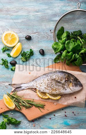 Cooking Raw Dorado Fish With Spinach, Rosemary, Olives, Herbs, Spices And Lemon Closeup On Wooden Cu