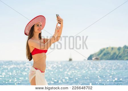 Attractive young woman making a selfie on the beach while enjoying a summer day during vacation in Flores Island, Indonesia