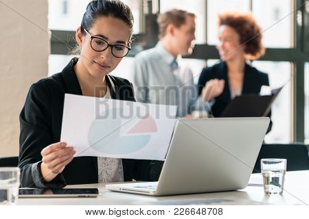 Hard-working young woman analyzing printed and electronic business information while sitting at desk in the office