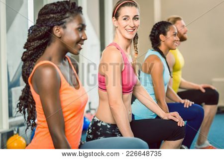 Full length of three young and beautiful determined people holding kettlebells while exercising Russian swing during functional training class at the gym
