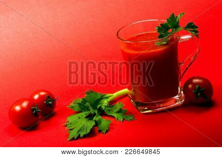 The Fresh Tomato Juice From Cherry Tomatoes With Celery And Parsley Is On Red Background.