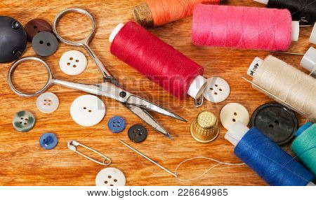 Photo Of Multi-colored Threads, Buttons And Scissors On A White Table Close-up