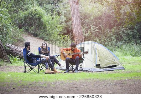 Just Having Fun In Nature - Three Friends Camping In A Forest.
