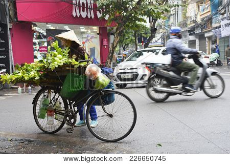 Hanoi, Vietnam - December 13th 2017. A Street Seller Sells Fruit And Vegetables From Her Bike At A B
