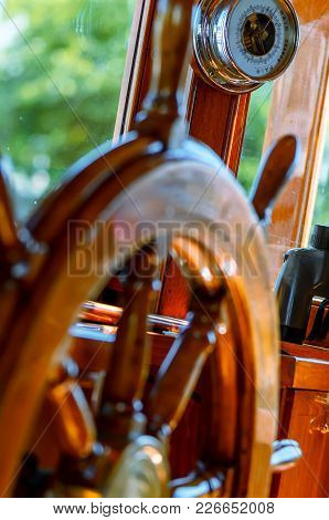 Red, Old, Lacquered, Wooden Steering Wheel On A Marine Yacht Close-up, Barometer And Binoculars In T