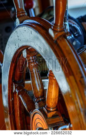 Yellow, Old, Lacquered, Wooden Steering Wheel On A Marine Yacht Close-up, Controls In The Background