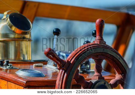 Red, Old, Lacquered, Wooden Steering Wheel On A Marine Yacht Close-up, Compass In The Background