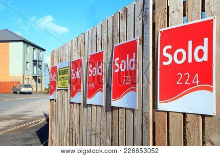 Row Of Sold Signs On The Wooden Fence At Construction Site