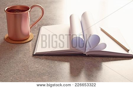 Notebook On Light Brown Grey Table Background. Heart Shape From Sheets Of Book. Opened Blank Decorat