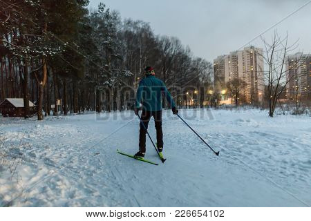 Photo From Back Of Male Skier In Blue Jacket In Winter Park On Background Of Houses