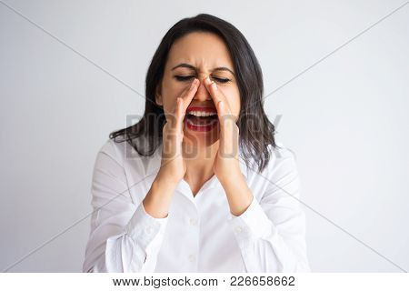 Closeup Portrait Of Middle-aged Beautiful Dark-haired Woman Cupping Hands Around Mouth And Shouting