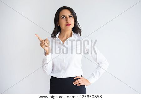 Closeup Portrait Of Pensive Middle-aged Beautiful Dark-haired Woman Looking Away And Raising Finger